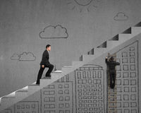 Climbing on stairs with man drawing on wall Stock Images