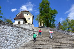 Climbing stairs. Three siblings climbing the famous 99 stairs of the Bled Church of the Assumption of Mary Stock Images