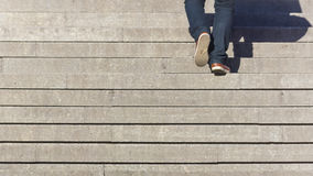 Climbing stairs. Young man in jeans coming up the stairs Royalty Free Stock Image