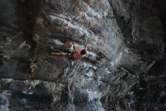 Climbing a steep rock face Stock Photo