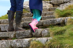 Parent & Child climbing steps. Mother and her daughter, both wearing wellington boots, climb the stone steps to reach St Michaels Mount, Cornwall Stock Photo