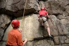Climbing team. A pair of rock climbers belaying one another at a crag Stock Image