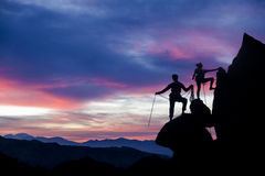 Climbing team on the edge. Climbers on the summit of a challenging cliff Royalty Free Stock Images