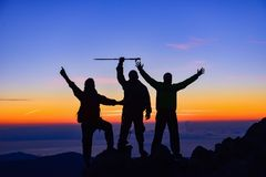 Climbing team on mountaintop. A silhouetted climbing team on the mountaintop at dusk Royalty Free Stock Photos
