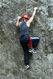 Climbing teen girl. Blonde teen girl climbing with a safety rope in place Royalty Free Stock Photography