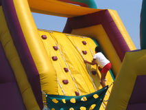 Climbing To The Top. A Child Climbing An Inflatable Obstacle Course Royalty Free Stock Photo