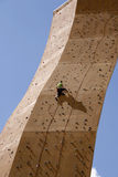 Climbing to the top. Man on climbing wall clambering to the top Royalty Free Stock Images