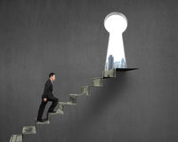 Climbing to top of money stairs with key hole Royalty Free Stock Photo
