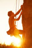 Climbing Training. Silhouettes of man climbing on a cliff at sunset stock photos