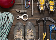 Climbing and travel equipment on dark background. Climbing and travel equipment: blue rope, red helmet, hammer, trekking shoes and other set  on dark wooden Royalty Free Stock Photography