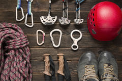 Climbing and travel equipment on dark background. Climbing and travel equipment  including rope, chocks, carabiner, eight, red helmet,  trekking shoes and other Royalty Free Stock Photo
