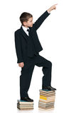 Climbing up the education stairs. A cute schoolboy is climbing up the book stairs on the white background Royalty Free Stock Photos