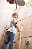 Climbing up on the high wall in an open shower area Stock Images