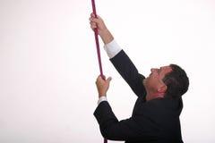 Climbing up II. Business man on his way up (metaphor, climbs rope) - vertical format stock photo