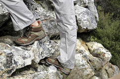 Climbing up. Side view of a pair of hiking boots worn by a person climbing up a rock face Royalty Free Stock Images