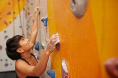 Climbing up. Young sportswoman gripping boulder when climbing up stock photos