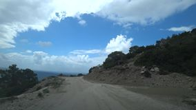 Climbing uphill along a narrow winding and broken road. The view from the car