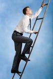 Climbing upwards. Photo of young businessman climbing upwards upon ladder Royalty Free Stock Images