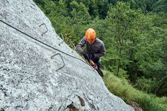 Climbing on via ferrata. People climbing on a via ferrata route in the mountains Royalty Free Stock Photography