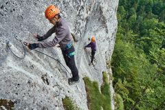 Climbing on via ferrata. People climbing on a via ferrata route in the mountains Royalty Free Stock Images