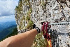 Climbing on via ferrata route. Arm and hand of a mountaineer climbing on a via ferrata route Stock Photography