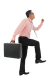 Climbing virtual ladder. Full body young Asian businessman climbing virtual ladder with briefcase, isolated on white background Royalty Free Stock Photos