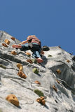 Climbing wall. Person climbing up an artificial climbing wall, view from directly below Stock Image