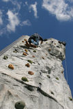 Climbing wall. Person climbing up an artificial climbing wall, view from directly below Royalty Free Stock Images
