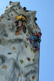 Climbing wall. Person climbing up an artificial climbing wall, view from directly below Stock Photography