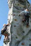 Climbing wall. Person climbing up an artificial climbing wall, view from directly below Royalty Free Stock Image