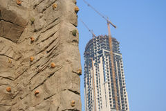 Climbing Wall. A climbing wall with a skscraper under construction in the background Stock Photo