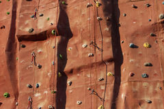 Climbing wall background with ropes. An artificial rock textured climbing wall background with holds, incuts, protrusions, hooks, carbines and ropes Royalty Free Stock Photography