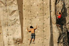 Climbing Wall I. Man and woman climbing on a wall Royalty Free Stock Photography