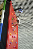 Climbing wall. Little girl climbs up the climbing wall Royalty Free Stock Photo