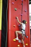 Climbing wall. Little girl climbs up the climbing wall Stock Photo