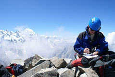 Climbing writes a message on the top of mountain. Climber writes records in a notebook on the top of mountain Stock Photos