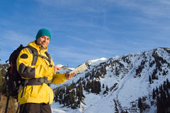 Climbing young adult with map and compass. Aerial view of mountain and blue sky Stock Photography