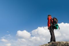 Climbing young adult at the top of summit Royalty Free Stock Photo