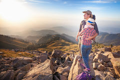 Climbing young couple at top of summit with aerial view Stock Photos
