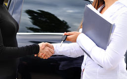 Clinching the purchase of a car and shaking hands. The saleslady and new female owner clinching the purchase of a car and shaking hands on the deal with one Royalty Free Stock Photos