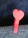 Clinged to my heart. A plastic pink clothes-pin with the shape of a heart on a blue towel Stock Photos