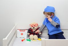 Clinic. Adorable child dressed as doctor playing with toy. Health exam by young medical worker. Educative and stock photography