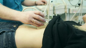 In the clinic doctor performs an abdominal ultrasound young blonde. stock video footage