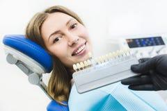 Clinica dentale Ricezione, esame del paziente Cura dei denti Dentista con i campioni di colore del dente che scelgono ombra per fotografie stock libere da diritti
