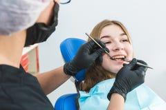 Clinica dentale Ricezione, esame del paziente Cura dei denti La ragazza subisce una visita odontoiatrica da un dentista immagini stock