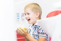 Clinica dentale Ricezione, esame del paziente Cura dei denti Ragazzino che tiene una mela mentre sedendosi in un dentario immagini stock libere da diritti