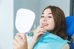 Clinica dentale Ricezione, esame del paziente Cura dei denti Sorridere della ragazza, guardante nello specchio dopo la a fotografie stock libere da diritti