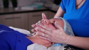 Clinica di bellezza Giovane donna che ottiene un massaggio facciale antinvecchiamento di rilassamento video d archivio