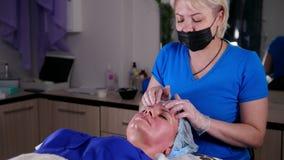 Clinica di bellezza Giovane donna che ottiene un massaggio facciale di rilassamento Massaggio della fronte archivi video