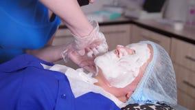 Clinica di bellezza La giovane donna ottiene ad una bellezza il trattamento antinvecchiamento Ungitura della maschera liquida sul archivi video